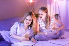 Liebevolle Mutter und Tochter, die auf dem Sofa sich entspannt Lizenzfreie Stockfotos