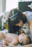 Liebevolle Mutter unterhält das Baby, das auf Windel liegt Lizenzfreie Stockfotografie