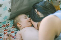 Liebevolle Mutter unterhält das Baby, das auf Windel liegt Lizenzfreies Stockfoto