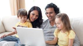 Liebevolle Muttergesellschaft, die laptopat Haus verwenden Lizenzfreie Stockfotos
