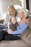 Liebevolle Muttergesellschaft mit dem Schätzchen, das zu Hause auf Schoss sitzt Lizenzfreie Stockbilder