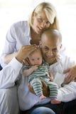 Liebevolle Muttergesellschaft mit Schätzchen in den Armen des Vatis Lizenzfreies Stockbild