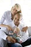 Liebevolle Muttergesellschaft mit schlafendem Schätzchen im Schoss des Vatis Stockfotografie