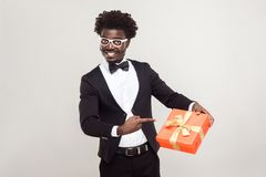 Liebevolle Paare Afrikanischer Geschäftsmann, der Finger auf Geschenkbox zeigt lizenzfreie stockfotografie