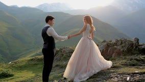 Liebevolle Paare auf dem Hintergrund der untergehenden Sonne und der Berge stock footage