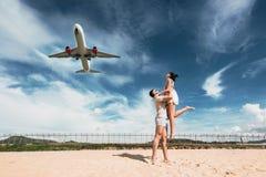 Liebevolle Paare auf dem Strand nahe dem Flughafen stockfoto