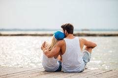 Liebevolle Paare auf dem umarmenden Strand beim Betrachten von Meer Lizenzfreies Stockbild