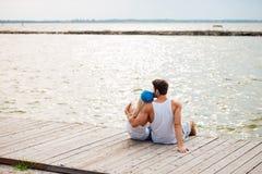 Liebevolle Paare auf dem umarmenden Strand beim Betrachten von Meer Stockfoto