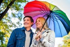 Liebevolle Paare auf einem Datum unter Regenschirm Lizenzfreie Stockbilder