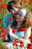 Liebevolle Paare auf einem Gebiet mit Mohnblumen Stockfotografie