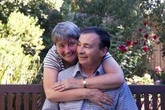 Liebevolle Paare auf einer Bank Lizenzfreie Stockfotos