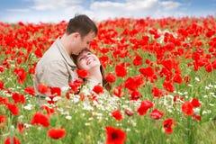 Liebevolle Paare auf rotem Mohnblumefeld lizenzfreie stockbilder
