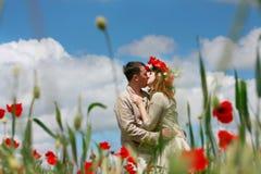 Liebevolle Paare auf rotem Mohnblumefeld lizenzfreies stockbild
