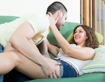 Liebevolle Paare auf Sofa Lizenzfreie Stockfotos
