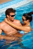 Liebevolle Paare beim Swimmingpoollächeln Stockbild