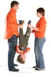 Liebevolle Paare in der orange Kleidung, die ihr Kind anhält stockfoto