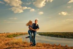 Liebevolle Paare, die auf Bank von Fluss umarmen Stockbilder