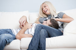 Liebevolle Paare, die auf Couch lachen und sich entspannen Stockbilder