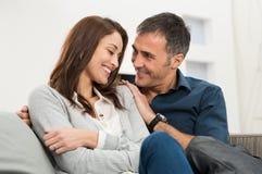 Liebevolle Paare, die auf Couch sitzen Stockfoto