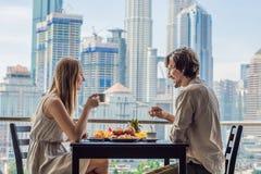 Liebevolle Paare, die auf dem Balkon frühstücken Frühstückstisch mit der Kaffeefrucht und -brot croisant auf einem Balkon gegen lizenzfreie stockfotografie