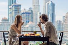 Liebevolle Paare, die auf dem Balkon frühstücken Frühstückstisch mit der Kaffeefrucht und -brot croisant auf einem Balkon gegen lizenzfreie stockfotos