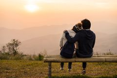 Liebevolle Paare, die auf dem Berg bei Sonnenuntergang umfassen stockbilder