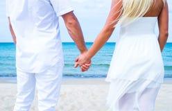 Liebevolle Paare, die auf dem Strand gehen und umfassen Stockbilder