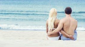Liebevolle Paare, die auf dem Strand sitzen und umfassen Stockfotos