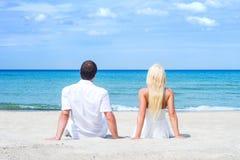 Liebevolle Paare, die auf dem Strand sitzen und umfassen Stockbild