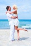Liebevolle Paare, die auf dem Strand umfassen Stockfotografie