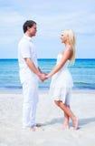 Liebevolle Paare, die auf dem Strand umfassen Lizenzfreie Stockfotografie
