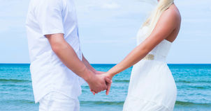 Liebevolle Paare, die auf einem Sommerstrand gehen und umfassen Lizenzfreies Stockfoto
