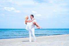 Liebevolle Paare, die auf einem Sommerstrand gehen und umfassen Stockbild
