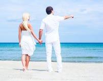 Liebevolle Paare, die auf einem Sommerstrand gehen und umfassen Stockfotos