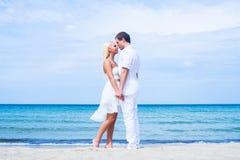Liebevolle Paare, die auf einem Sommerstrand gehen und umfassen Stockfoto
