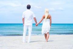 Liebevolle Paare, die auf einem Sommerstrand gehen und umfassen Lizenzfreie Stockbilder
