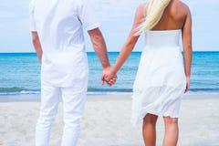 Liebevolle Paare, die auf einem Sommerstrand gehen und umfassen Lizenzfreie Stockfotografie