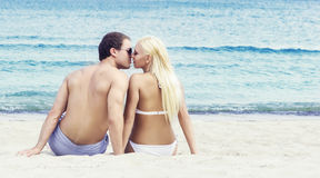 Liebevolle Paare, die auf einem tropischen Sommerstrand sitzen und küssen Lizenzfreie Stockbilder