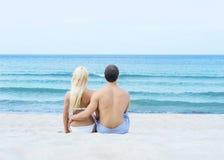 Liebevolle Paare, die auf einem tropischen Sommerstrand sitzen und umfassen Lizenzfreie Stockbilder