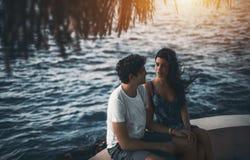 Liebevolle Paare, die auf Erholungsortpier sitzen Lizenzfreie Stockbilder