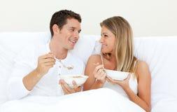 Liebevolle Paare, die auf ihrem Bett frühstücken Lizenzfreie Stockfotografie