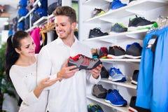 Liebevolle Paare, die auf neuen Turnschuhen im Sportspeicher entscheiden Lizenzfreie Stockfotografie