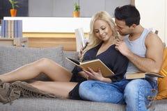 Liebevolle Paare, die auf Sofa umfassen Lizenzfreie Stockfotos
