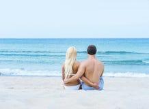Liebevolle Paare, die auf Sommerstrand sitzen und umfassen Stockbild