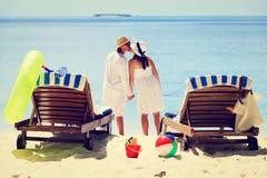 Liebevolle Paare, die auf tropischem Strand küssen Stockbilder