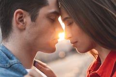 Liebevolle Paare, die bei Sonnenuntergang umfassen stockbilder