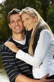 Liebevolle Paare, die beim Parklächeln umarmen Lizenzfreie Stockfotos