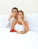 Liebevolle Paare, die Champagne mit Erdbeeren trinken Lizenzfreie Stockfotografie