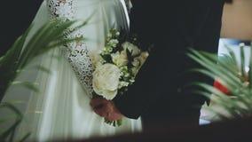 Liebevolle Paare, die einen Hochzeitsblumenstrauß in den Händen halten stock footage