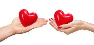 Liebevolle Paare, die Herzen in den Händen lokalisiert auf Weiß halten Lizenzfreies Stockbild